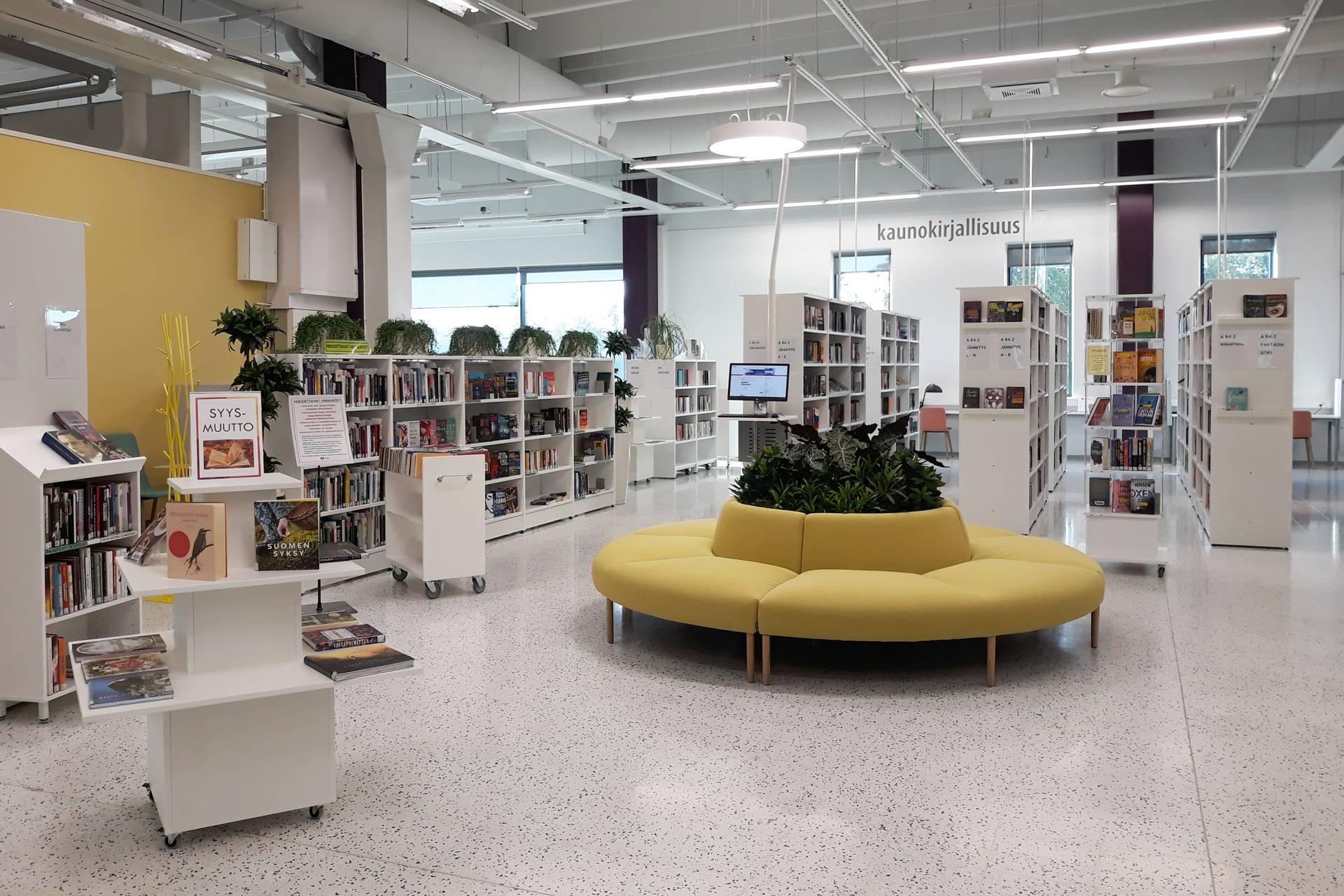 Kaupunginkirjasto Valon aulatila Kuvassa kirjojen esittelyhyllyjä, kirjahyllyjä sekä keltainen, pyöreä sohva, jonka keskellä viherkukkia.