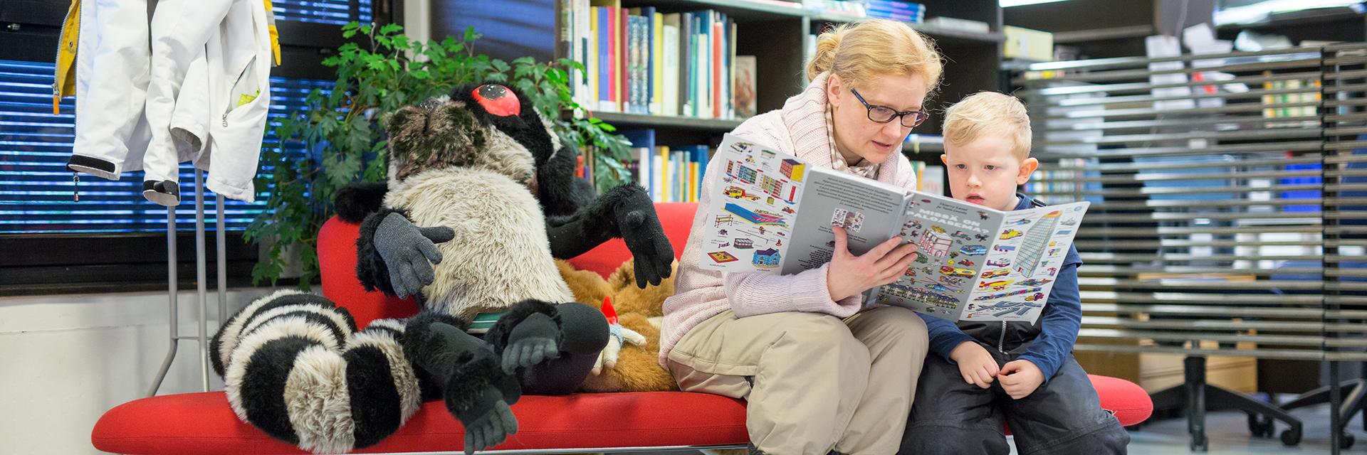 Nainen ja lapsi istuvat punaisella sohvalla. Naisella kädessä iso kuvakirja, jota tutkailevat yhdessä.