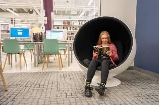 Nuori tyttö istuu pallotuolissa lukemassa kirjaa. Taustalla lastenosaston tietokoneita.