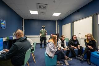 Kuvassa pelitila, jossa tummansiniset seinät. Kolme henkilöä istuu ohjaimet kädessä ja takana yksi henkilö on virtuaalilasit päässä.