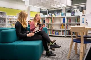 Kaksi tyttöä istuvat tummanvihreällä sohvalla lukemassa kirjoja. Taustalla näkyy kirjahylly.