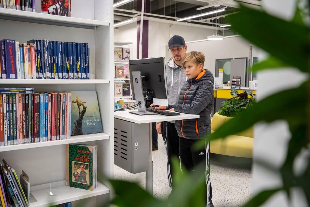 Isä ja poika seisovat tietokoneen ääressä. Vasemmalla etualalla näkyy kirjahyllyä ja oikealla takana keltaista sohvaa.