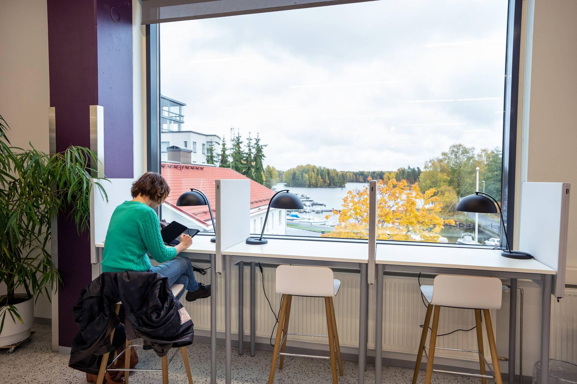 Ihminen istuu työpöydän ääressä, ison ikkunan luona.