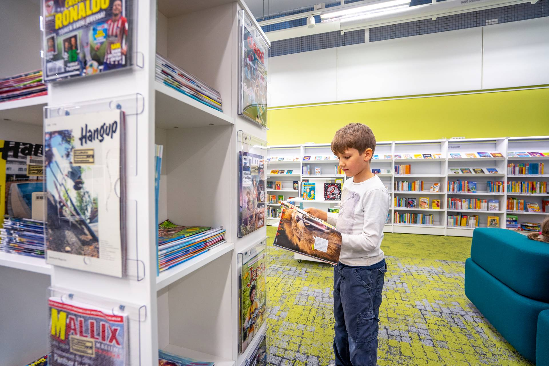 A boy holding a magazine in front of a shelf for magazines.