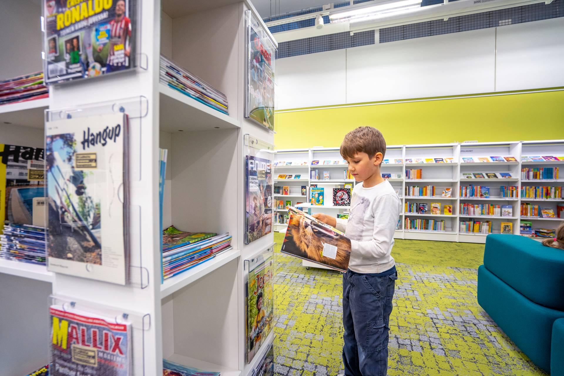 Poika pitelee käsissään lehteä. Etualalla näkyy lehtitorni, jossa lehtiä säilytetään.