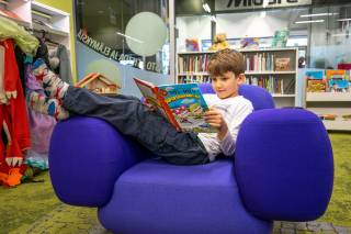 Poika istuu violetissa nojatuolissa ja lukee Tatu ja Patu- kuvakirjaa. Taustalla kirjahyllyjä.