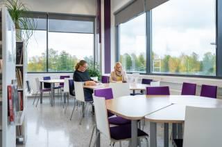 Kuvassa pyöreitä työskentelypöytiä, joiden ääressä istuu kaksi ihmistä. Taustalla isoja ikkunoita, joista näkyy puiden latvoja.