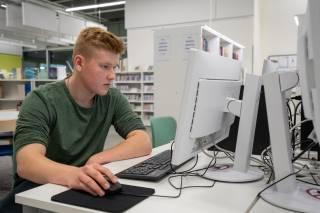 Poika istuu tietokoneen ääressä, katsoo tietokoneen ruutua.
