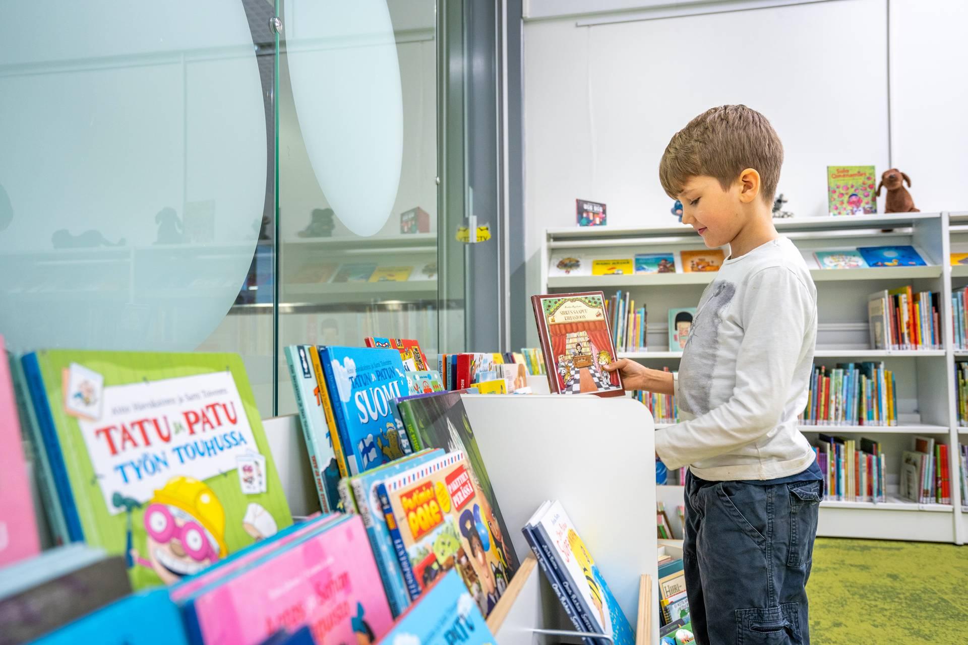 Poika seisoo kuvakirjakärryn edessä ja silmäilee kirjoja.
