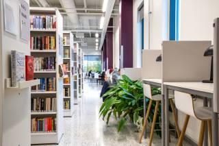 Kuva kirjaston hyllyjen välistä. Kuvassa kirjahyllyjä ja työskentelypisteitä