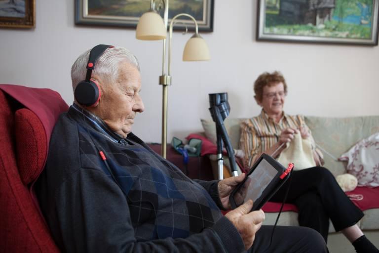 Iäkkäämpi mies kuuntelee äänikirjaa kuulokkeet päässä. Taustalla iäkkäämpi nainen kutoo.