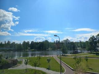 Vehreä puistonäkymä, taustalla kanava. Taivaalla poutapilviä ja vaaleansininen taivas. Aurinko pilkistää pilven takaa.